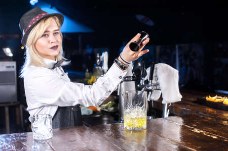 Sweet barmaid decorates colorful concoction in cocktail bars