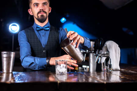 Young mixologist intensely finishes his creation in the bar Reklamní fotografie - 159574506