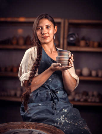 Pottery girl shows the finished clay product in the pottery workshop. Handicraft production. Reklamní fotografie
