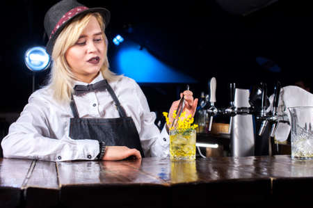 Professional woman tapster places the finishing touches on a drink