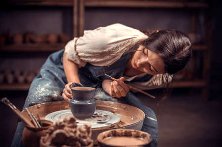 Beautiful young woman master demonstrates the process of making ceramic dishes using the old technology. Folk handicraft.