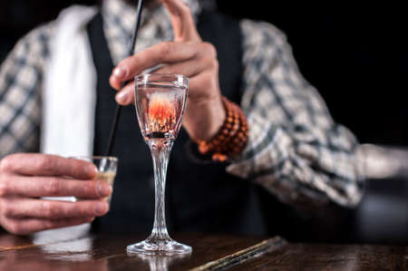 Portrait of bartender creates a cocktail in cocktail bars