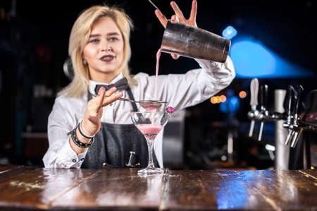 Girl bartender mixes a cocktail in the porterhouse