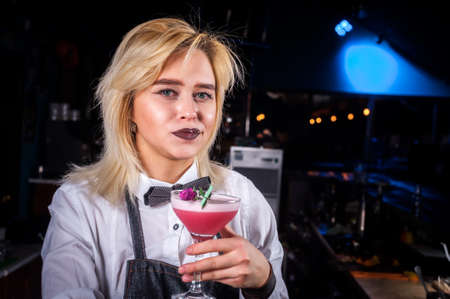 Young girl barman creates a cocktail while standing near the bar counter in pub Reklamní fotografie - 159582910