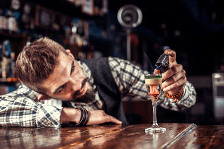 Bearded bartending decorates colorful concoction in the night club Reklamní fotografie - 159579455