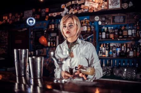 Girl barman formulates a cocktail on the taproom Reklamní fotografie