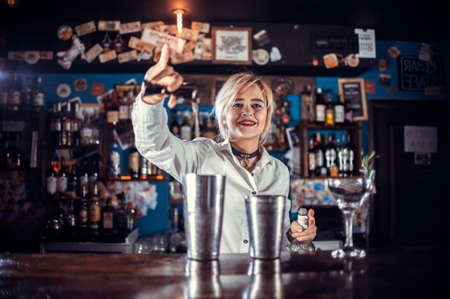 Girl bartender concocts a cocktail at the public house Reklamní fotografie