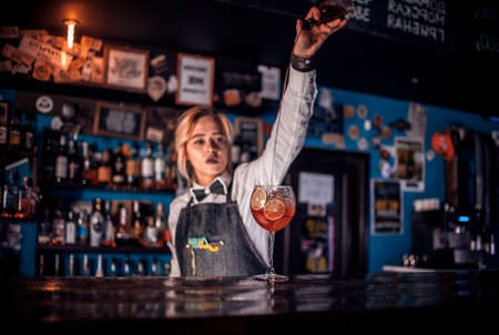 Girl barman concocts a cocktail at the taproom