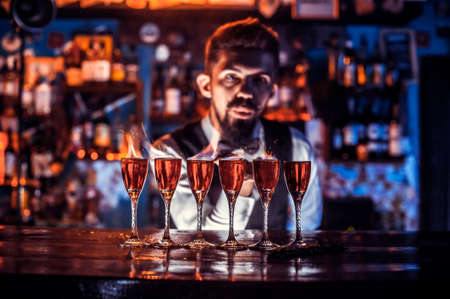 Bearded bartender formulates a cocktail at the nightclub