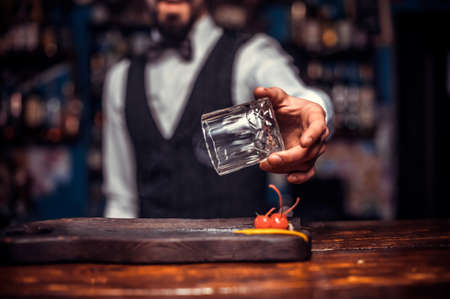 Bearded tapster demonstrates the process of making a cocktail behind bar