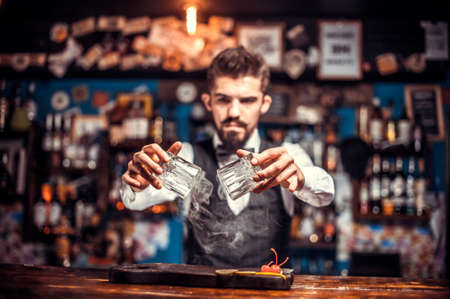 Charming mixologist pouring fresh alcoholic drink into the glasses behind bar