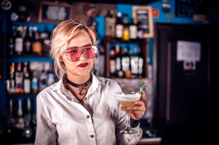 Girl barman formulates a cocktail in the beerhall