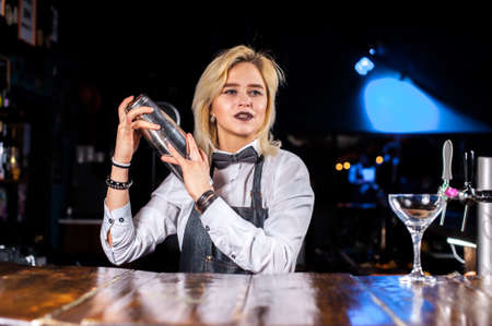 Pretty girl bartending demonstrates his skills over the counter in the nightclub