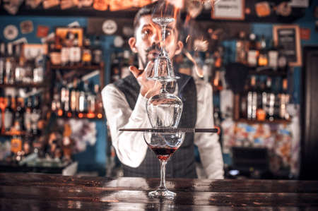 Professional Female bartender creates a cocktail on the bar