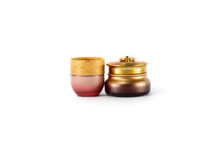 Gold and pink cosmetics containers isolate on white background photo