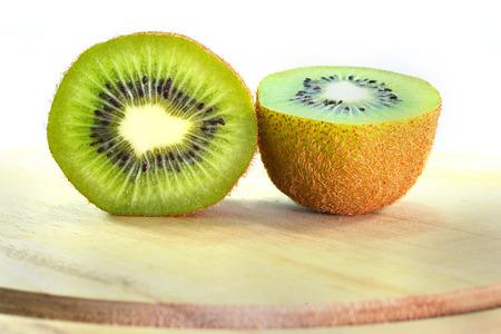 a portion: a kiwi portion on wood chopping block