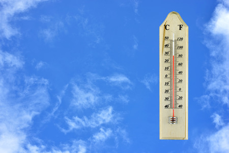 termometer: thermometer on wood plate blue sky background Stock Photo