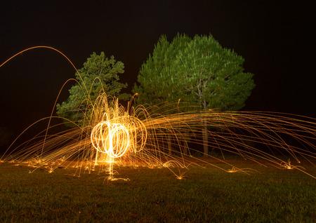 steel wool: spinning fire ball by burning steel wool - fire twirl Stock Photo