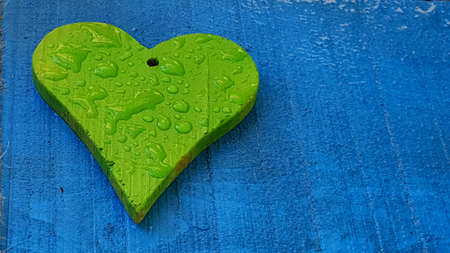 patterns and designs of green wooden heart on blue background with rain drops