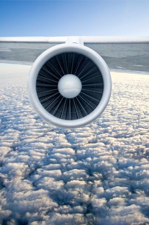 Airplane engine and wings on the blue sky and white clouds photo