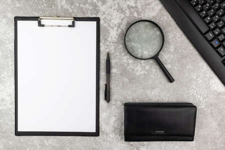 Office workstation or business background with magnifying glass, purse, keyboard and clipboard with blank paper on a grey stone background viewed from overhead. Flat lay, top view