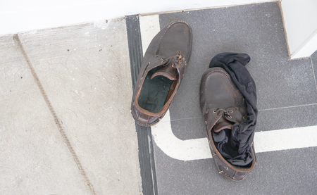 dirty shoes and black socks on the floor in the office., shoe and sock has foul stinky., health concept. cleaning concept.