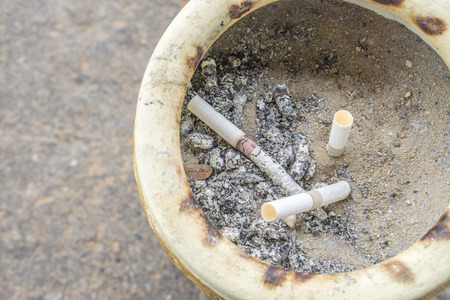 Big pile of put out cigarettes in an ashtray.