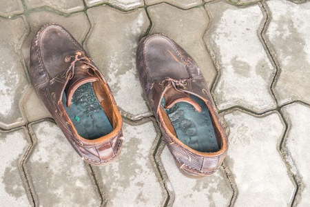 pair of old brown leather shoes on cement background Stock Photo