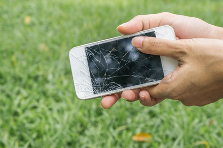 Hands holding broken mobile smartphone , Cracked smartphone in hand holding. sad concept. damage concept. technology concept. 스톡 콘텐츠
