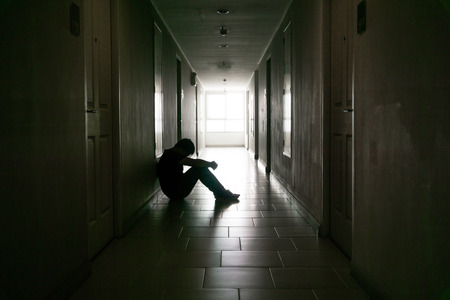 Silhouette of business man sitting alone., Sad and Serious Male sit and hug his knee alone of closeing office.With his reflect shadow. Dramatic moment. sad concept., hurt concept. lonely