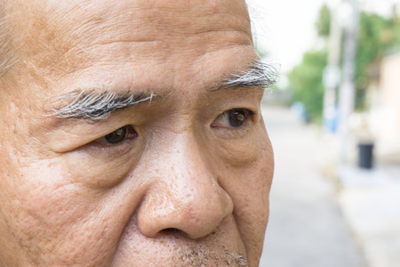 Closeup old asian mans eye and eyebrow. with copy space for text. aging concept., Old asian man glabrous head., stand on the street with copy space Stock Photo