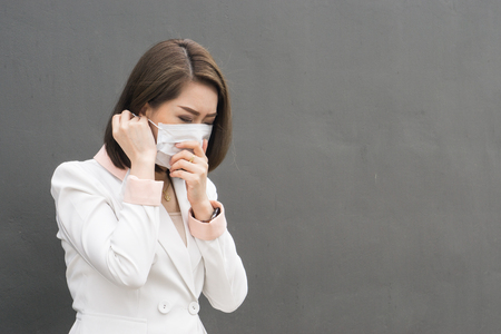 Asian woman wear protective face mask in pollution city with coughing., copy space for text