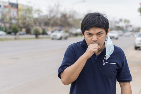 Asian man in the street wearing protective masks., Sick man with flu wearing mask and blowing nose into napkin as epidemic flu concept on the street.