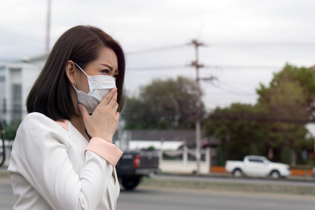 Woman suffer from sick and wearing face mask., asian woman in protective mask feeling bad on the street in the city with air pollution. Banque d'images