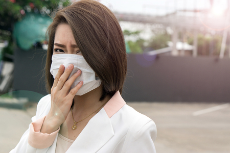 Woman suffer from sick and wearing face mask., asian woman in protective mask feeling bad on the street in the city with air pollution. Stok Fotoğraf - 96654180