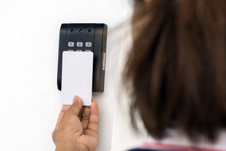 Door access control - young woman holding a key card to lock and unlock door., Keycard touch the security system to access the door
