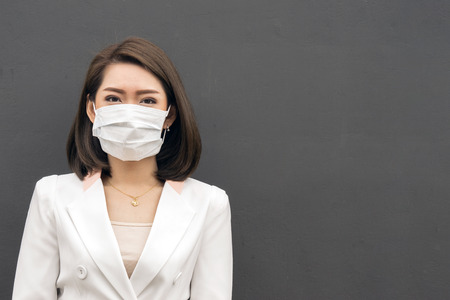 Woman suffer from sick and wearing face mask., asian woman in protective mask feeling bad on the street in the city with air pollution. 스톡 콘텐츠