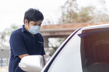 Robber and the car thief in a mask opens the door of the car and hijacks the car., Sick man with flu wearing mask and blowing nose into napkin as epidemic flu concept open his car. Stock Photo