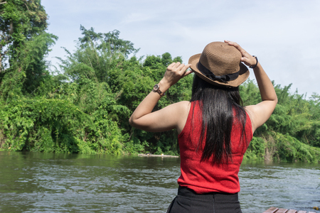 Happy Asian girl red shirt and brown hat on the river in nature background, Relax time on holiday concept travel., Thailand river kwai and typical landscape kanchanaburi., with copy space for text Stock Photo