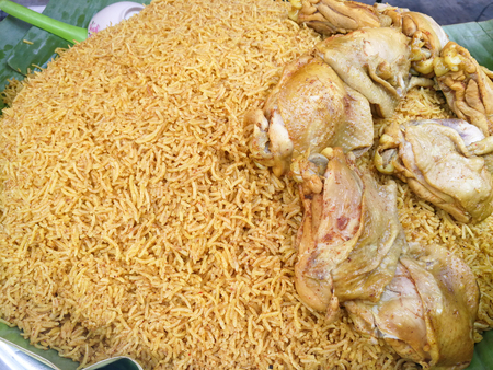 Muslim yellow rice with chicken (Koa Mook Gai) in a big pot ready to served with a spicy ginger side sauce, cucumber and tomato sliced., The food sell in thailand. Stock Photo