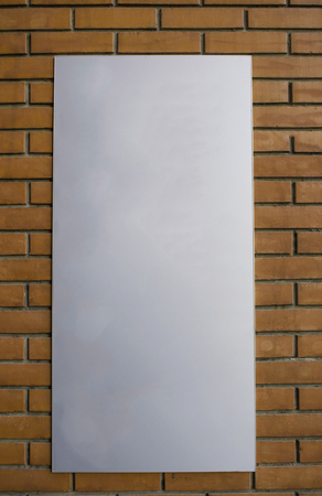 Vertical blank billboard on a red brick wall