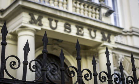 Museum sign and entrance in background out of focus, iron fence in foreground focused; selective focus Редакционное