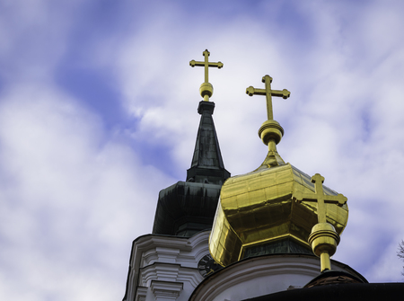Three golden orthodox church crosses against blue sky and clouds