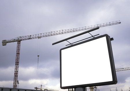 Blank billboard in front of industrial crane, building construction site concept Фото со стока