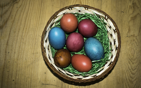 Colorful Easter eggs in a basket on a beautiful aged wooden table background wiht copy space on the left