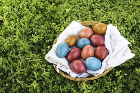 Easter eggs in a basket in green grass, empty copy space on the left side of image