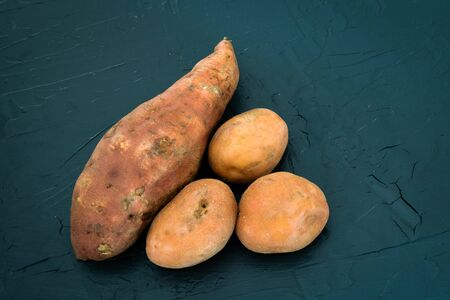 Sweet potato next to a regular potatoes on a black background