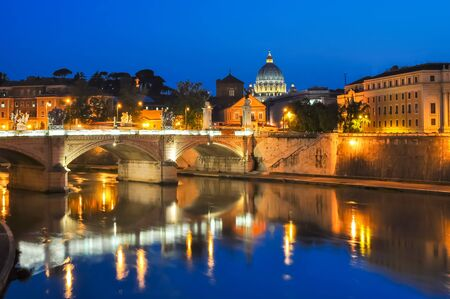 Victor Emmanuel bridge over Tiber river with St. Peter's Cathedral as background at night, Rome, Italy