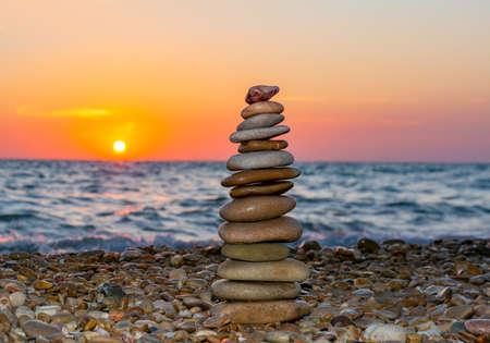 Pyramid of stones on pebble beach at sunset 免版税图像