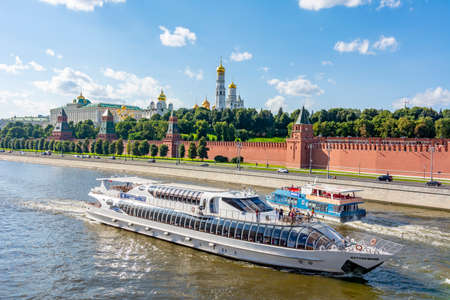 Moscow, Russia - August 2020: Boats sailing on Moskva river with Moscow Kremlin at background